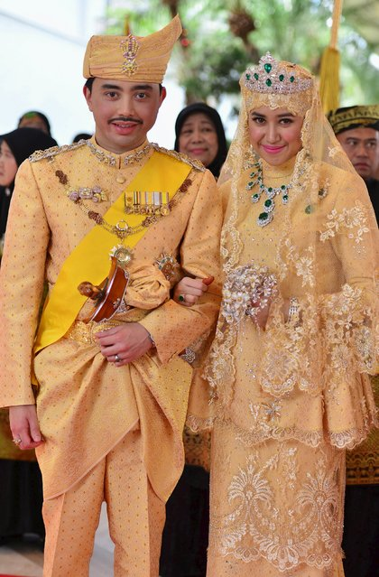 "Brunei's newly wed royal couple, Prince Abdul Malik and Dayangku Raabi'atul 'Adawiyyah Pengiran Haji Bolkiah, pose for photographers after the ""bersanding"" or enthronement ceremony at their wedding in the Nurul Iman Palace in Bandar Seri Begawan April 12, 2015. (Photo by Ahim Rani/Reuters)"