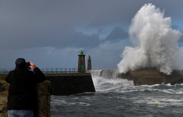 A man takes a picture of the waves as they crash against a lighthouse in the northern Spanish village of Viavelez, Spain January 13, 2017. (Photo by Eloy Alonso/Reuters)