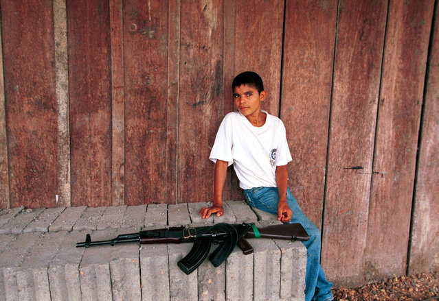 A boy sits near an AK-47 assault rifle at a FARC check point February 26, 2001 in Cristales, Colombia. The FARC (Revolutionary Armed Forces of Colombia) is the country's largest rebel group and has been waging an insurgency against the government for decades, at the cost of some 3,000 lives a year. (Photo by Carlos Villalon/Newsmakers)