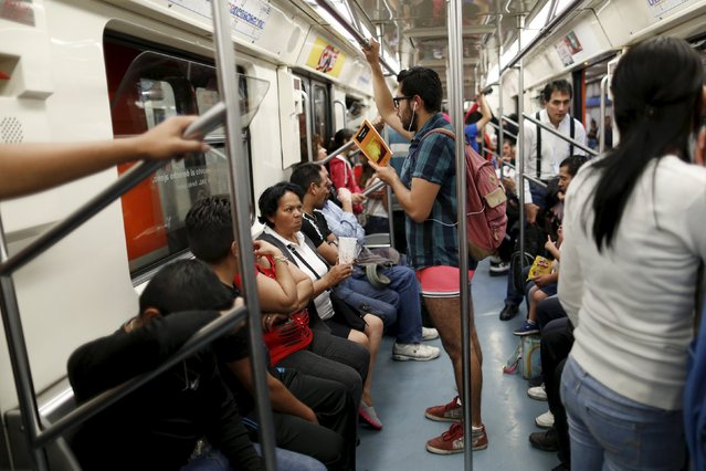 """A passenger not wearing pants stands as he reads a book inside a subway train during the """"No Pants Subway Ride"""" in Mexico City, Mexico, February 21, 2016. (Photo by Carlos Jasso/Reuters)"""