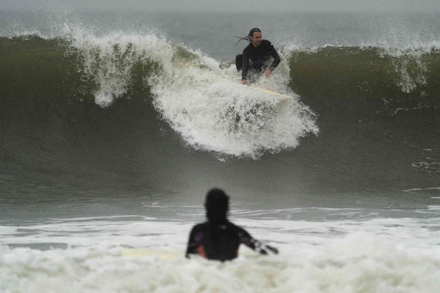 A surfer enjoys as big wave on a closed beach as Tropical Storm Henri brings strong surf and high winds to the area, Sunday, August 22, 2021, in the Queens borough of New York. (Photo by John Minchillo/AP Photo)