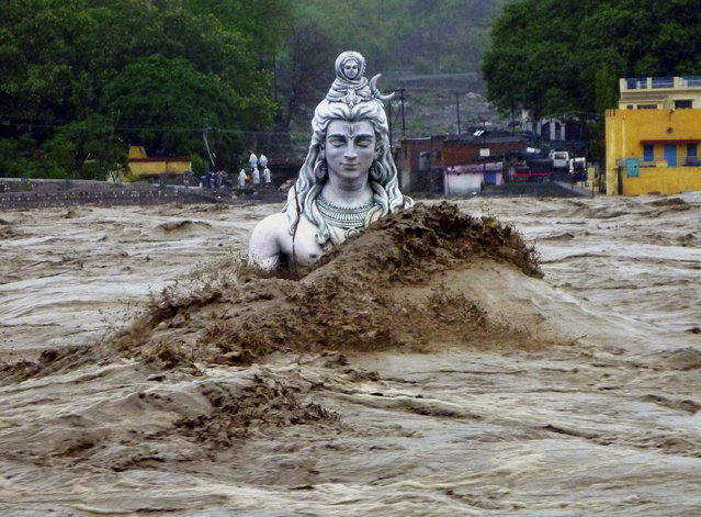 A submerged idol of Hindu Lord Shiva stands in the flooded River Ganges in Rishikesh, in the northern Indian state of Uttarakhand, India, Tuesday, June 18, 2013. (Photo by AP Photo)