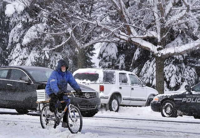 Tony Berard makes his way down Highland Road in Waterford, past a car that had slid off the road, on his way back from work in White Lake, Michigan. (Photo by Daniel Mears/Detroit News)