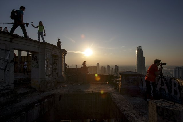 Visitors enjoy the sunset on the roof top of an abandoned building in Bangkok April 19, 2015. (Photo by Athit Perawongmetha/Reuters)