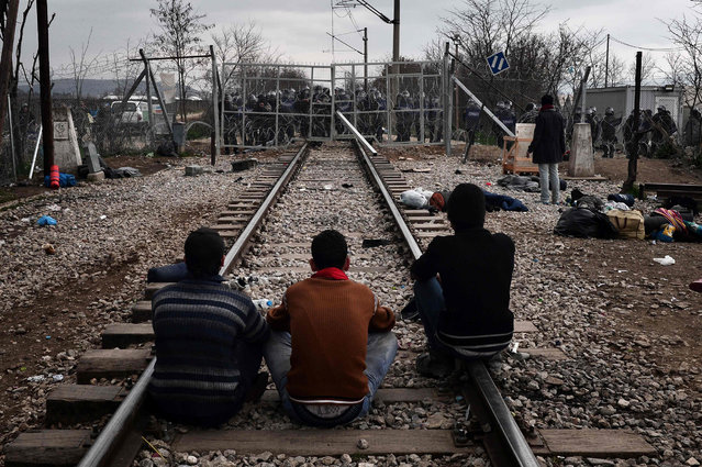 Migrants sit on rail tracks as they face a fence guarded by Macedonian police at the Greek-Macedonian border, near the Greek village of Idomeni, on February 29, 2016, where more than 7,000 people are stranded. Macedonian police fired tear gas as a group of some 300 Iraqi and Syrians forced their way through a Greek police cordon and raced towards a railway track between the two countries, as anger mounted over travel restrictions on migrants.  (Photo by Louisa Gouliamaki/AFP Photo)