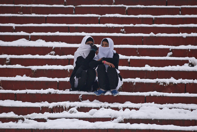 Schoolgirls sit on steps of a stadium covered with snow as they watch India's Republic Day celebrations on a cold winter day in Srinagar January 26, 2017. (Photo by Danish Ismail/Reuters)