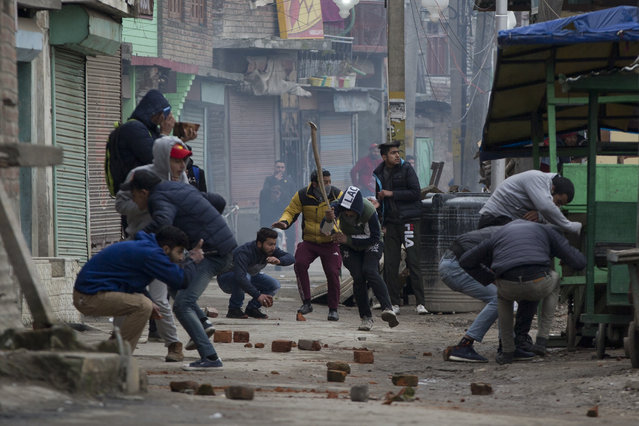 Kashmiri protesters run for cover as they during clash with Indian police men in Srinagar, Indian controlled Kashmir, Tuesday, February 26, 2019. Indian forces in Indian portion of Kashmir used tear gas shells to quell protests against raids on key separatist leaders by Indian intelligence officers. (Photo by Dar Yasin/AP Photo)