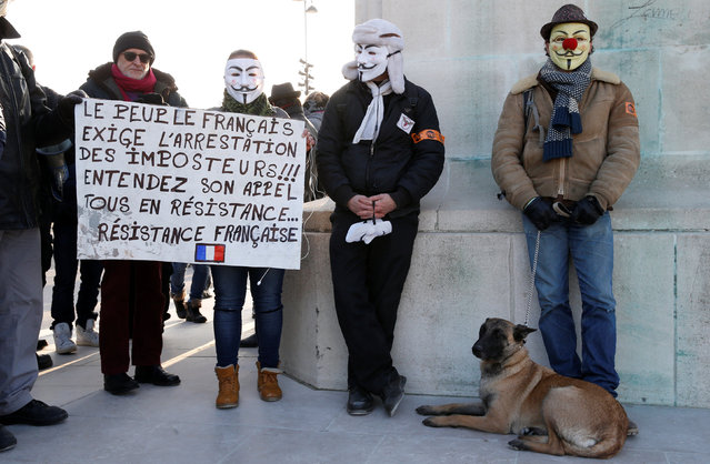 """People wearing Guy Fawkes masks attend a protest against anti-police violence in Paris, France, January 26, 2017. The slogan reads in part, """"The French demand the arrest of the impostors"""". (Photo by Jacky Naegelen/Reuters)"""