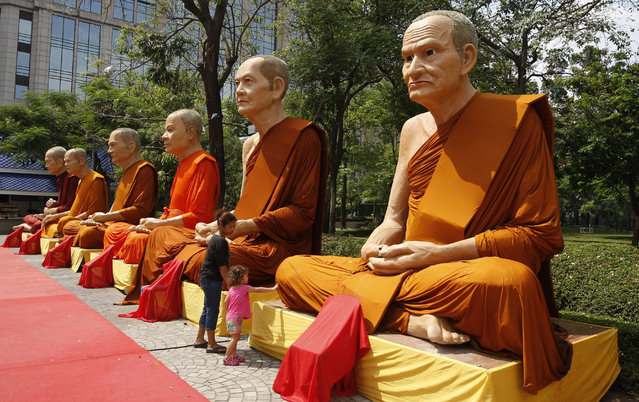 A young girl touches the knee of a giant statue in a row of Thai Buddhist monks erected in a park in Bangkok, Thailand, 20 April 2015. Members of Thailand's National Reform Council created after a military coup in May 2014 to implement national reforms meant to ensure clean politics, have begun a week long debate on the draft on constitutional changes. (Photo by Barbara Walton/EPA)