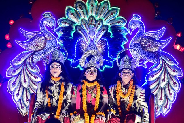 Youths dressed as Hindu deities lord Rama (L), Sita (C) and Laxman sit on a tableau during a festival procession, in Allahabad, India on October 11, 2021. (Photo by Sanjay Kanojia/AFP Photo)