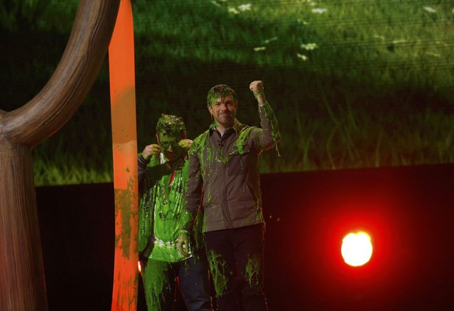 "Actors Jason Sudeikis (R) and Josh Gad react after being ""slimed"" on stage at Nickelodeon's 2016 Kids' Choice Awards in Inglewood, California March 12, 2016. (Photo by Mario Anzuoni/Reuters)"