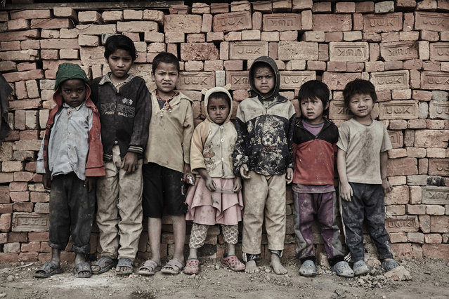 A group of child labourers gather for a portrait in the midst of the brick kiln in Kathmandu Valley, Nepal, 21 February 2015. (Photo by Jan Moeller Hansen/Barcroft Images)