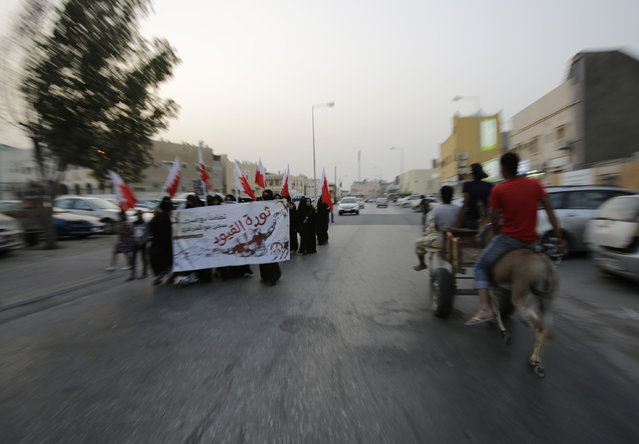 "A small group of Bahraini women, carrying national flags and a banner supporting political prisoners, march quickly between police patrols, on the lookout for violators of a protest ban, in Manama, Bahrain, Friday, May 1, 2015. The government denied permission for Labor Day protests, so protesters in several opposition areas went out in small groups for quick marches between police patrols. The banner reads: ""Revolution of Chains, in solidarity with Jaw central prison inmates"". (Photo by Hasan Jamali/AP Photo)"