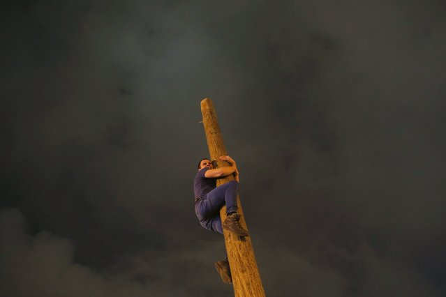 A man climbs up a wooden pole during Maslenitsa celebrations at Gorky park in Moscow, Russia, March 13, 2016. Maslenitsa is widely viewed as a pagan holiday marking the end of winter and is celebrated with pancake eating and shows of strength, while the Orthodox Church considers it as the week of feasting before Lent. (Photo by Maxim Shemetov/Reuters)