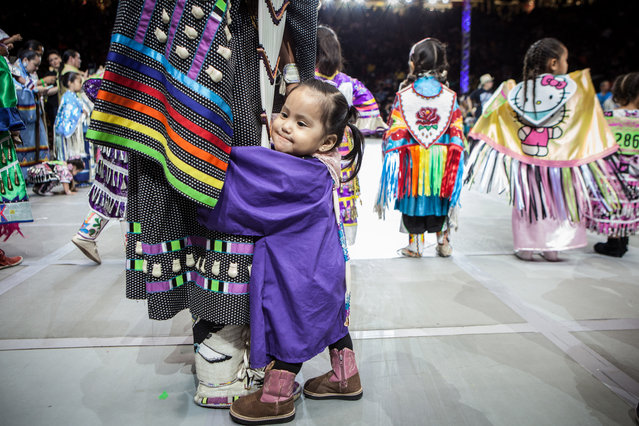 Peyton Moses, 18 months, clings to her mom, Heather Blackgoat, from Kirtland, N.M., before the Tiny Tot Girls competition in the 32nd annual Gathering of Nations in Albuquerque N.M., Saturday, April 25, 2015. (Photo by Mark Holm/AP Photo)