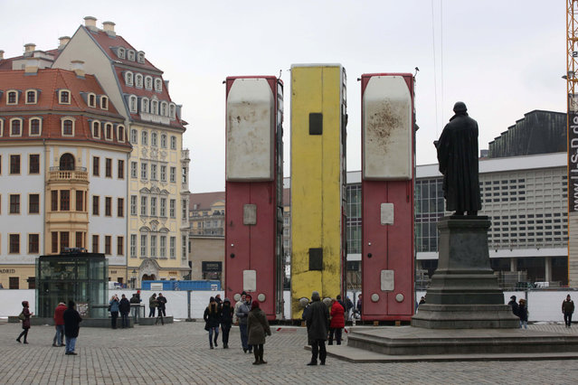 """People walk next to the art instalation """"Monument"""" by Syrian artist Manaf Halbouni, made from three passenger busses in Dresden, Germany February 8, 2017. (Photo by Matthias Schumann/Reuters)"""
