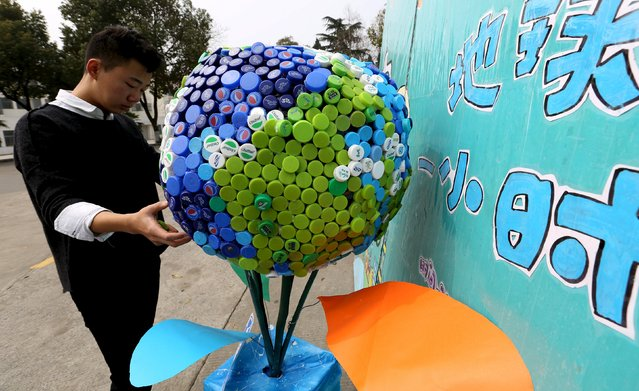 A college student adjusts a model globe made of 2016 bottle caps to mark the upcoming Earth Hour in Zhenjiang, Jiangsu province, March 19, 2016. (Photo by Reuters/Stringer)