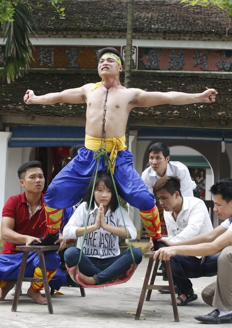 Nguyen Manh Quan (top), 26, a civil servant, carries a girl using his throat area as he performs during a showcase of the traditional Thien Mon Dao kung fu at Du Xa Thuong village, southeast of Hanoi, Vietnam May 10, 2015. (Photo by Reuters/Kham)