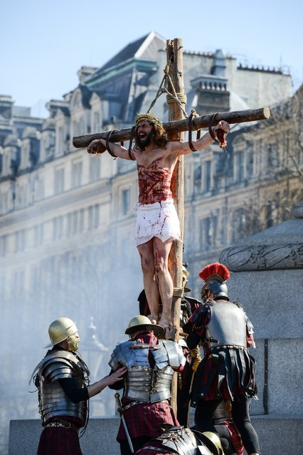 """Actor James Burke-Dunsmore is raised on to a crucifix whilst playing Jesus during The Wintershall's """"The Passion of Jesus"""" in front of crowds on Good Friday at Trafalgar Square on March 25, 2016 in London, England. (Photo by Chris Ratcliffe/Getty Images)"""
