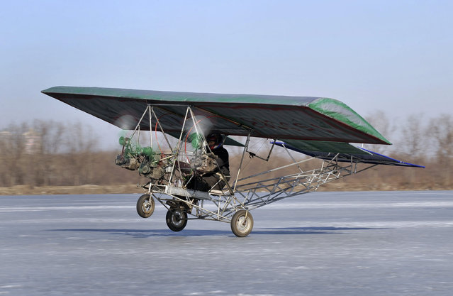 Ding Shilu, an automobile mechanic, carries out a test-flight for his self-made aircraft at a frozen reservoir in Shenyang, Liaoning province February 25, 2011. The aircraft which weights about 130 kg (287 lbs) and made of recycled materials including three motorbike engines and plastic cloth, cost about 2600 yuan ($395), local media reported. (Photo by Reuters/Stringer)