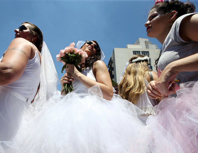 """Revellers take part in the annual """"Marry me"""" carnival block parade in the main street in Sao Paulo, Brazil February 18, 2017. (Photo by Paulo Whitaker/Reuters)"""