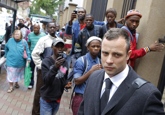 South African Paralympic athlete Oscar Pistorius (R) leaves the High Court in Pretoria during the lunch break on day 3 of his murder trial, in Pretoria, South Africa, March 5, 2014. Pistorius is standing trial for the premeditated murder of his model girlfriend Reeva Steenkamp in February 2013. (Photo by Kim Ludbrook/EPA)