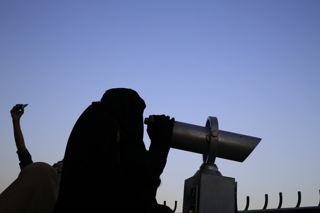 This Tuesday, May 5, 2015 photo shows an Egyptian woman looking through a telescope on the observation deck of the Cairo Tower in the Zamalek district in Cairo, Egypt. For most, the niqab is a choice. They do so out of their own interpretation of the Quran and the hadith, a collection of traditions and anecdotes about the Prophet Muhammad, believing that a woman's body should be covered out of modesty. (Photo by Hassan Ammar/AP Photo)
