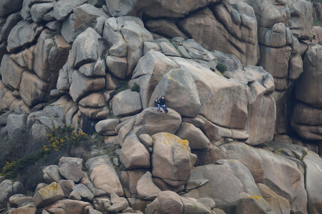 People sit on rocks in Perros-Guirec, France, March 11, 2016. (Photo by Stephane Mahe/Reuters)