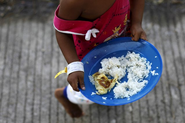 A Rohingya migrant child, who recently arrived in Indonesia by boat, holds her plate of breakfast at a shelter in Kuala Langsa, in Indonesia's Aceh Province, May 19, 2015. (Photo by Reuters/Beawiharta)