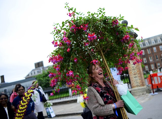 A woman carries a fuschia plant on the final day of the Royal Horticultural Society's Chelsea Flower Show in London, Britain, May 23, 2015. (Photo by Dylan Martinez/Reuters)