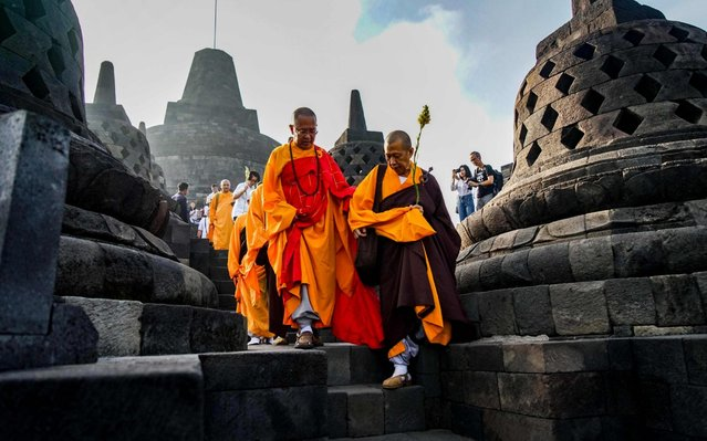 Buddhist monks pray on the eve of Buddha's birthday also known as Vesak celebrations, at Borobudur temple in Magelang, Central Java province, on May 18, 2019. Buddhists are celebrating Vesak, which commemorates the birth of Buddha, his attaining enlightenment and his passing away on the full moon day of May which falls on May 18 this year. (Photo by Oka Hamied/AFP Photo)