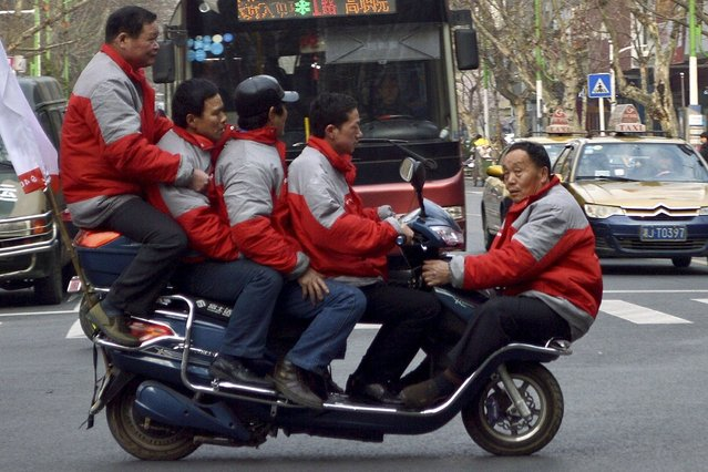 Five men sit on a electric bicycle as they cross a street in Changde, Hunan province. (Photo by Reuters/Stringer)