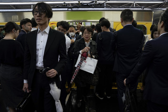 In this Tuesday, May 21, 2019, photo, commuters make their way past people waiting in line as they get off a Yamanote Line train during morning rush hours at Shinjuku Station in Tokyo. Trains are always packed during morning and evening rush hours as they are notoriously known. It's so densely packed that passengers don't even have to grab a handrail to stand upright despite swaying. There are shoves from commuters who can't afford to wait another few minutes for a next train, but no one growls in irritation. It's usually forgiven with just a little nod, a gesture of apology. (Photo by Jae C. Hong/AP Photo)