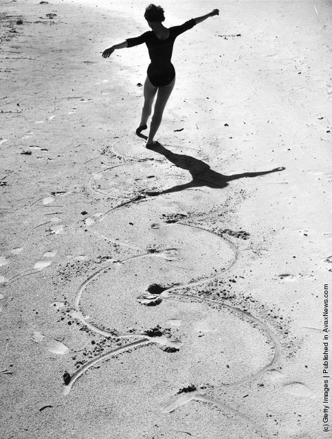 1955: A ballet dancer draws circles in the sand with the points of her toes
