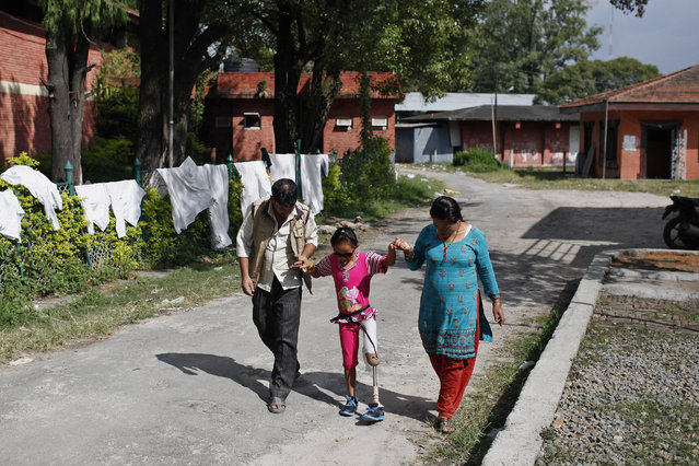 In this October 16, 2015 photo, amputee victim in the massive 2015 Nepal earthquake, Khendo Tamang, 8, center, walks with the assistance of her mother Yagnsen and family friend Chitra Bahadur after receiving a new prosthesis at a clinic in Kathmandu, Nepal. (Photo by Niranjan Shrestha/AP Photo)