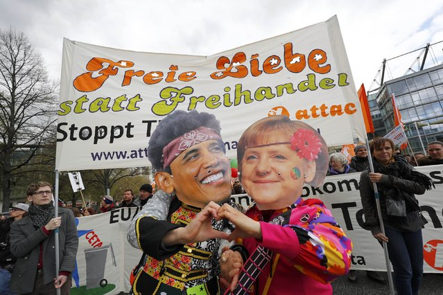 Protesters wearing masks depicting German Chancellor Angela Merkel and U.S. President Barack Obama as they demonstrate against Transatlantic Trade and Investment Partnership (TTIP) agreement ahead of Obama's visit in Hannover, Germany April 23, 2016. (Photo by Kai Pfaffenbach/Reuters)