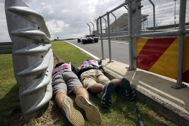 Photographers lie downy by the side of the track to shoot the cars passing by during the first free practice at the Silverstone racetrack, in Silverstone, England, Friday, July 12, 2019. The British Formula One Grand Prix will be held on Sunday. (Photo by Luca Bruno/AP Photo)