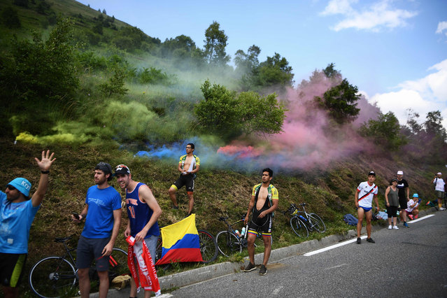 In this file photo taken on July 20, 2019 Cycling enthusiasts wait for riders on the roadside as coloured smoke billows during the fourteenth stage of the 106th edition of the Tour de France cycling race between Tarbes and Tourmalet Bareges. (Photo by Anne-Christine Poujoulat/AFP Photo)