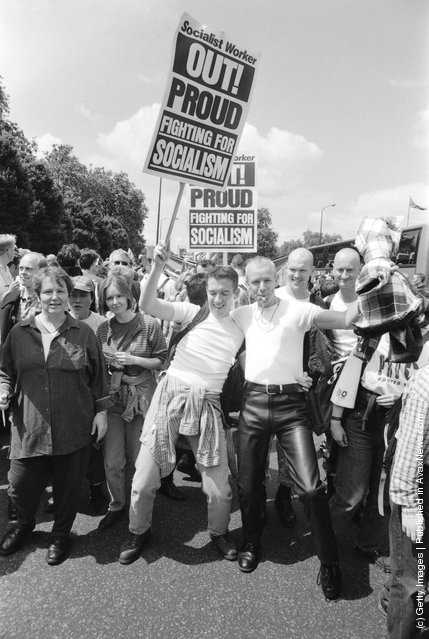 Revellers taking part in the Gay Pride parade, carrying a placard that reads 'Out, Proud, Fighting for Socialism' in London, England