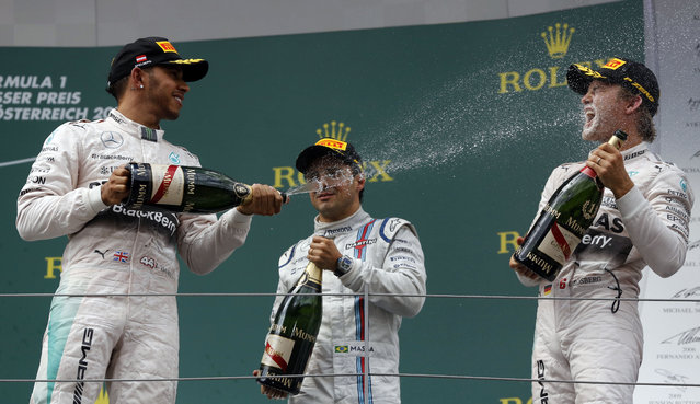 Second placed Mercedes driver Lewis Hamilton of Britain, left sprays champagne on the winner Mercedes driver Nico Rosberg of Germany, as third placed Williams driver Felipe Massa of Brazil, center, looks on, following the Formula One Grand Prix race, at the Red Bull Ring in Spielberg, southern Austria, Sunday, June 21, 2015. (AP Photo/Darko Bandic)
