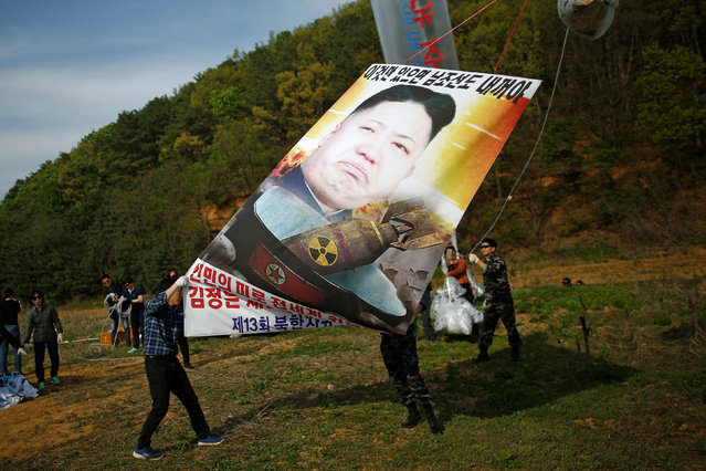 Park Sang-hak (L), a North Korean defector and leader of an anti-North Korea civic group, holds a banner depicting North Korean leader Kim Jong Un with nuclear, tied on a balloon, near the demilitarized zone in Paju, South Korea, April 29, 2016. (Photo by Kim Hong-Ji/Reuters)