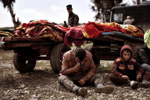 Relatives mourn as bodies of Iraqi residents of west Mosul killed in an airstrike targeting Islamic State (IS) group jihadists are placed and covered with blankets on carts on March 17, 2017. (Photo by Aris Messinis/AFP Photo)