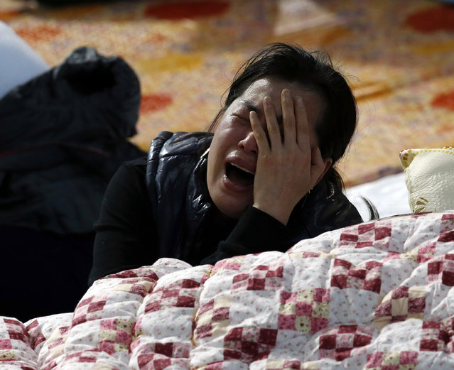 A family member of a missing passenger onboard the Sewol ferry which capsized on Wednesday, cries as she checks the newly announced list of the dead, at a gym in Jindo April 20, 2014. South Korean prosecutors investigating the ferry disaster said on Sunday they would seek to extend the detention of the ship's captain and two other crew by 10 days as they tried to determine the cause of the accident that may claim more than 300 lives. (Photo by Kim Kyung-Hoon/Reuters)