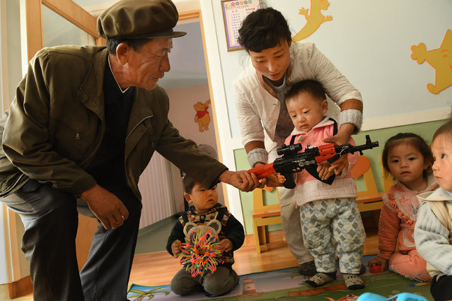 A 2- 3 year-old-child holds a toy machine gun during a media tour of a day care / preschool center at Jangchon cooperative farm on the outskirts of  Pyongyang, North Korea on May 4, 2016. Man at left is said to be a farmer there. The homes had vegetable gardens in the front, solar panels on the roofs but didn't appear to be very populated. (Photo by Linda Davidson/The Washington Post)
