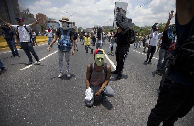Demonstrators stand on a main road during clashes with the Bolivarian National Guard during a protest in Caracas, Venezuela, Monday, April 10, 2017. (Photo by Ariana Cubillos/AP Photo)