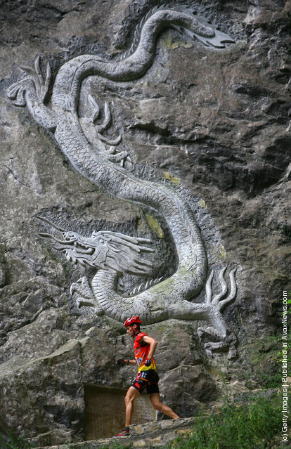 A contestant runs past a dragon engraved on the crag as he competes during the caving session of the Wulong Mountain Quest
