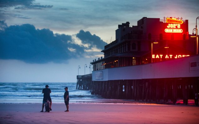 Beachgoers chat next to the Main Street Pier in Daytona Beach, Florida, USA, 03 September 2019. Hurricane Dorian, a powerful Category 3 storm that was expected to hammer Florida this week, will now remain largely offshore. (Photo by Jim Lo Scalzo/EPA/EFE/Rex Features/Shutterstock)