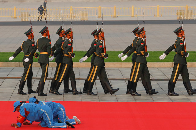 Workers clean a red carpet before a wreath laying ceremony at the Monument to the People's Heroes in Tiananmen Square, marking the 70th anniversary of the founding of the People's Republic of China, in Beijing, China on September 30, 2019. (Photo by Thomas Peter/Reuters)