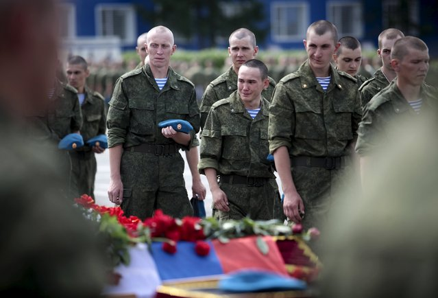 Soldiers react as they walk past coffins of troops killed after the collapse of a section of a barracks during a funeral ceremony in Omsk, Russia, July 14, 2015. At least 23 soldiers were killed when a military barracks collapsed in Russia's Omsk region, Russian news agencies said on Monday. (Photo by Dmitry Feoktistov/Reuters)