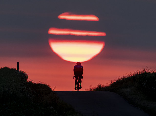 A man rides his bike on a small path as the sun rises in Frankfurt, Germany, Thursday, June 27, 2019. (Photo by Michael Probst/AP Photo)